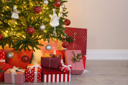 Photo for Pile of gift boxes near Christmas tree indoors - Royalty Free Image