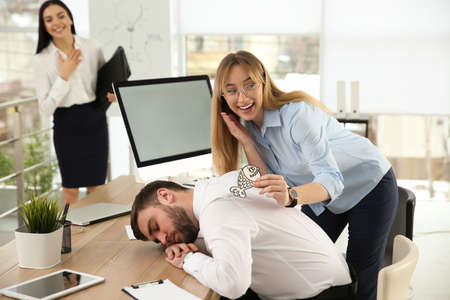 Photo pour Young woman sticking paper fish to colleague's back while he sleeping in office. Funny joke - image libre de droit