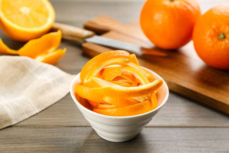 Photo for Fresh orange fruit peels on wooden table - Royalty Free Image