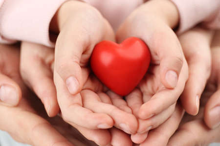 Photo for Parents and kid holding red heart in hands, closeup. Family day - Royalty Free Image