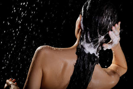 Photo pour Young woman washing hair while taking shower on black background - image libre de droit