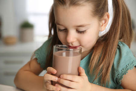 Photo for Cute little child drinking tasty chocolate milk in kitchen, closeup - Royalty Free Image
