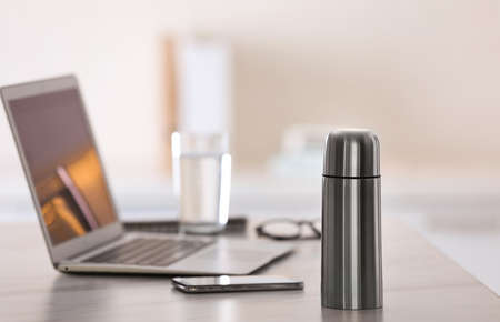 Photo for Thermo bottle on table in modern office - Royalty Free Image