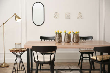 Photo pour Stylish wooden dining table and chairs in room. Interior design - image libre de droit