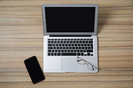 Photo for Modern laptop, smartphone and glasses on wooden table, flat lay. Space for design - Royalty Free Image