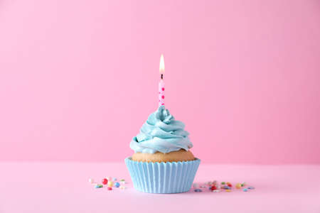 Photo pour Delicious birthday cupcake with burning candle and sprinkles on pink background - image libre de droit