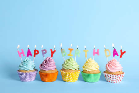 Photo pour Birthday cupcakes with burning candles on light blue background - image libre de droit