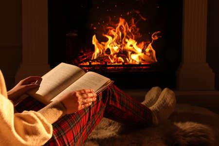 Photo pour Woman with book near fireplace at home, closeup - image libre de droit