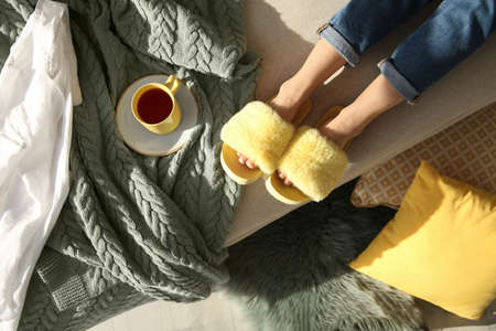 Photo for Woman with cup of tea wearing soft comfortable slippers at home, top view - Royalty Free Image