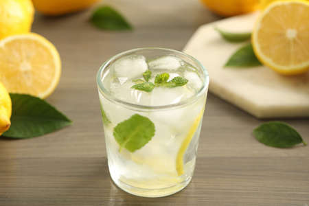 Photo for Cool freshly made lemonade in glass on wooden table, closeup - Royalty Free Image