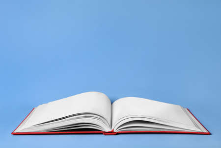 Photo for Open book with red cover on light blue background. Space for text - Royalty Free Image