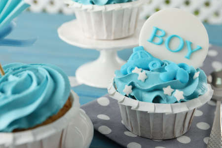 Photo for Delicious cupcakes with light blue cream and toppers for baby shower on table, closeup - Royalty Free Image