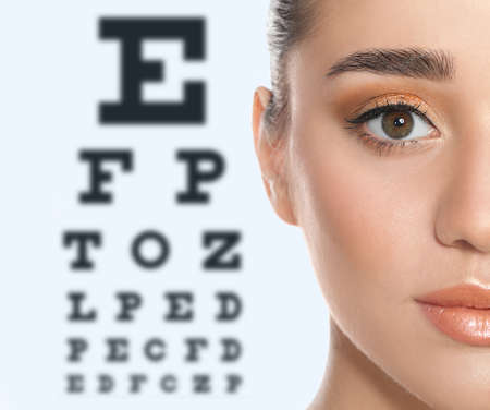 Photo for Young woman and blurred eye chart on background. Visiting ophthalmologist - Royalty Free Image