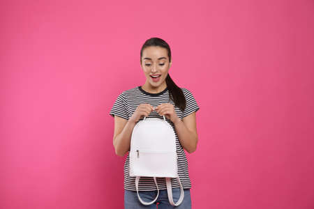 Photo for Excited young woman with stylish leather backpack on pink background - Royalty Free Image