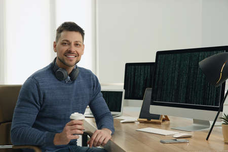 Photo for Happy programmer with headphones and coffee working at desk in office - Royalty Free Image