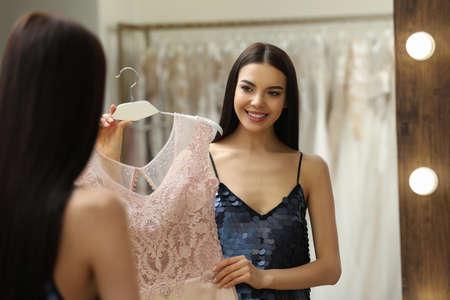 Photo pour Woman choosing dress in rental clothing salon - image libre de droit