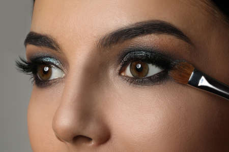 Photo for Applying dark eye shadow with brush onto woman's face, closeup. Beautiful evening makeup - Royalty Free Image