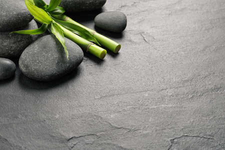 Photo pour Spa stones and bamboo stems on grey table. Space for text - image libre de droit