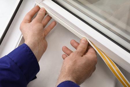 Photo pour Worker putting rubber draught strip onto window indoors, closeup - image libre de droit
