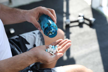 Photo for Sportsman with bottle of pills in gym, closeup. Doping concept - Royalty Free Image