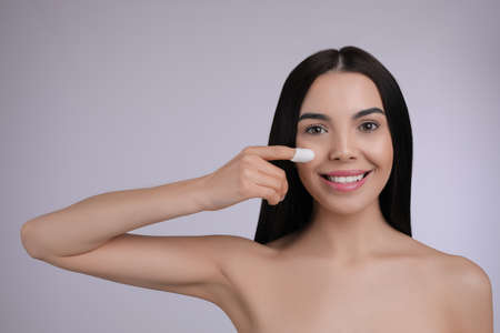 Photo for Woman using silkworm cocoon in skin care routine on light gray background. Space for text - Royalty Free Image
