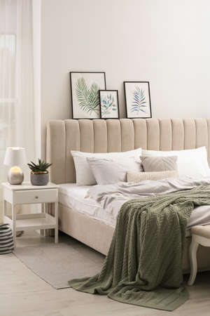 Photo for Bed with stylish gray linens near white wall in room - Royalty Free Image