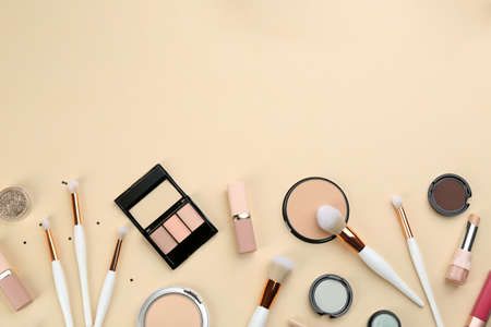 Photo for Different makeup brushes and cosmetic products on beige background, flat lay. Space for text - Royalty Free Image
