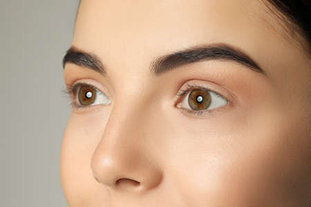Photo pour Young woman with beautiful eyebrows on gray background, closeup - image libre de droit