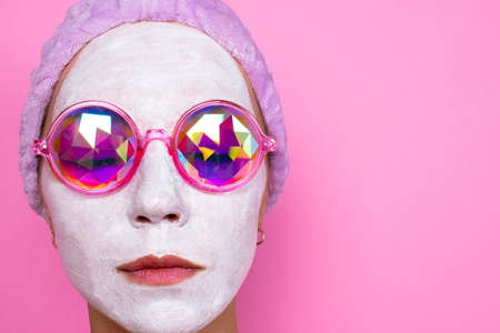 Photo pour girl in cosmetic white mask and pink glasses smiles on a pink background. Spa concept - image libre de droit