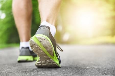 Foto de Athlete runner feet running on road closeup on shoe. woman fitness sunrise jog workout wellness concept. - Imagen libre de derechos
