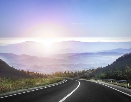 Foto de Highway road against mountains and a sky at the sunrise or sunset. - Imagen libre de derechos