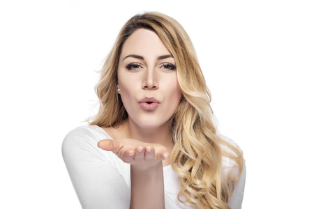 Blonde woman sending air kiss over white background