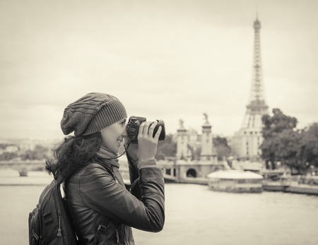 Girl photographs of Paris and the Eiffel Tower.