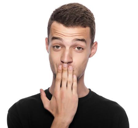 Man with hand covering his mouth on white background.
