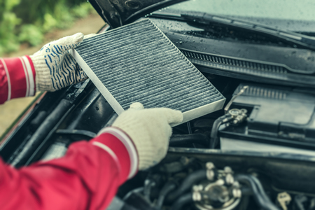 Photo pour The auto mechanic replaces the cars interior filter. - image libre de droit