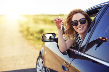Photo pour An attractive woman in a car holds a car key in her hand. - image libre de droit