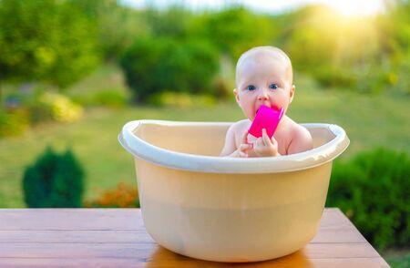 Photo pour The baby bathes in a bath in the garden on a summer evening. - image libre de droit