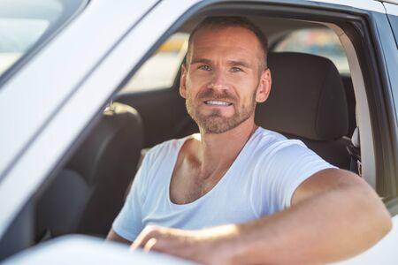 Photo pour A man driving a white car. - image libre de droit