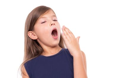 Photo for Little girl is yawning. Isolated on a white background. - Royalty Free Image