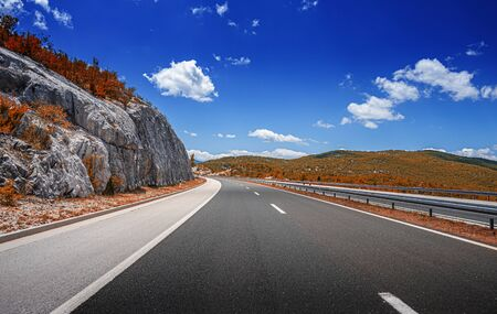 Photo pour Mountain highway with blue sky and rocky mountains on a background - image libre de droit