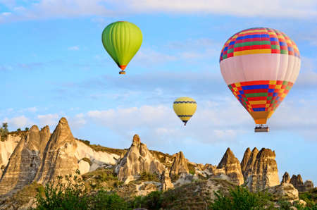 Hot air balloon flying over spectacular landscape of fairy chimneys carved in volcanic tuff by erosion. Cappadocia, Turkey