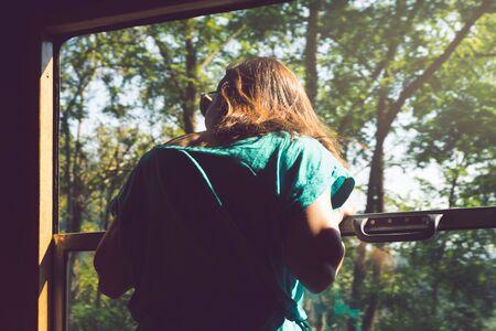Girl traveler looking through train window in vacation.