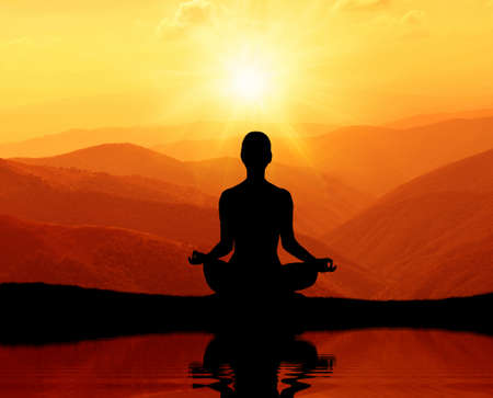 Man meditating in yoga position on the top of mountains