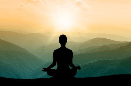 Foto de Yoga silhouette on the mountain in sunrays. the dawn sun - Imagen libre de derechos