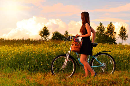 young beautiful girl with a bicycle on the green field