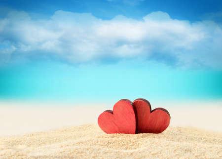 Foto de Two wooden red hearts on the summer beach - Imagen libre de derechos