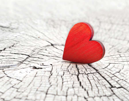 red wooden heart on a cracked wooden background