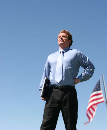 american business man standing under a blue sky