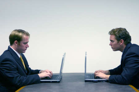 Business men in black suits face each other as they sit down around a conference table typing on their laptops