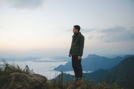Photo pour young man standing on hill is wearing green coat - image libre de droit